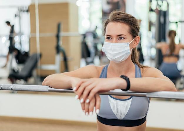 Donna che si allena in palestra durante la pandemia con maschera