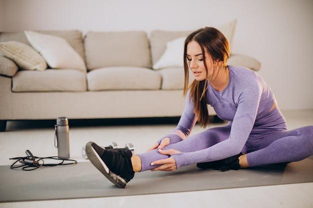 Donna che si allena a casa sul tappetino usando manubri e corda per saltare