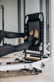 Woman training pilates on the reformer