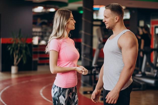 Женщина тренируется вместе с тренером в тренажерном зале