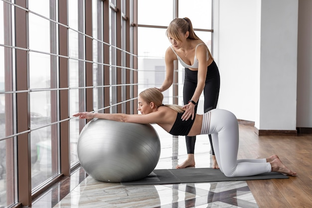Woman training with ball and mat