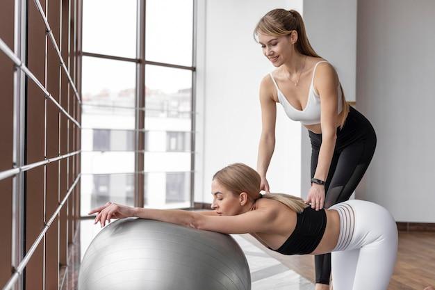 ボールミディアムショットでトレーニングする女性