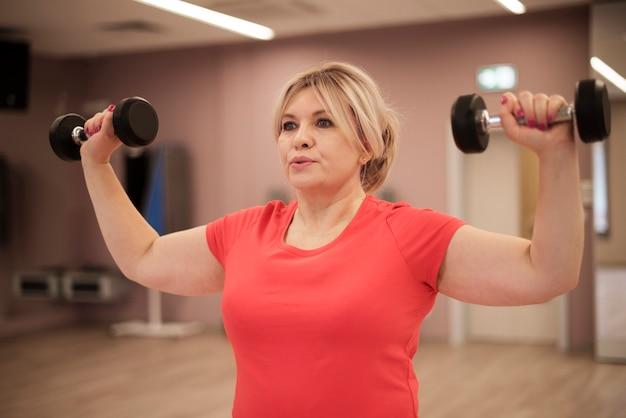 Тренировка женщины с гантелями