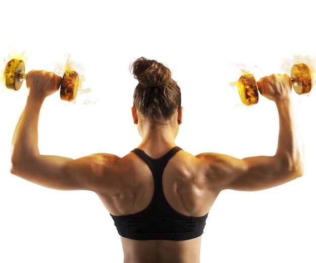 燃えるようなダンベルでトレーニングする女性