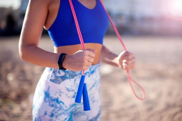 屋外の縄跳びでトレーニングの女性。人、フィットネス、ヘルスケアのコンセプト