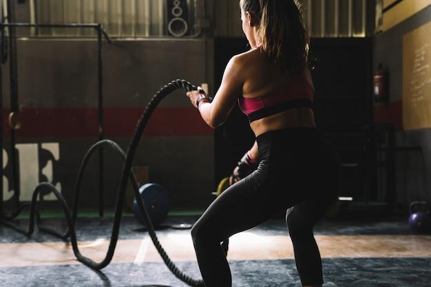 체육관에서 밧줄으로 훈련하는 여자
