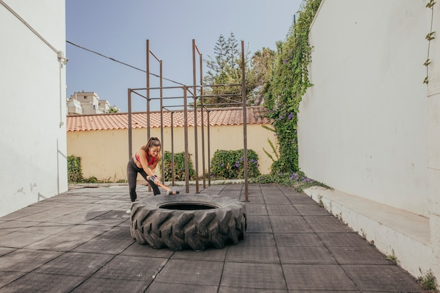 Woman training with tractor wheel