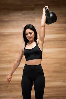 Тренировка женщины с тяжелой атлетикой в спортзале