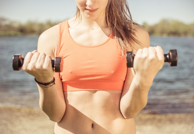 Woman training with weights. concept about training outdoor in the nature
