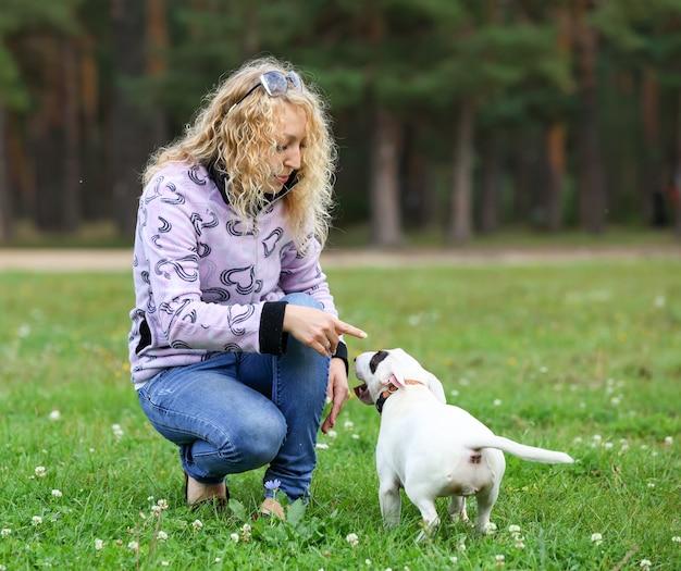 Женщина тренирует собаку в парке