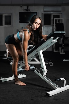 Woman trains in the gym athletic woman trains with dumbbells, pumping his biceps