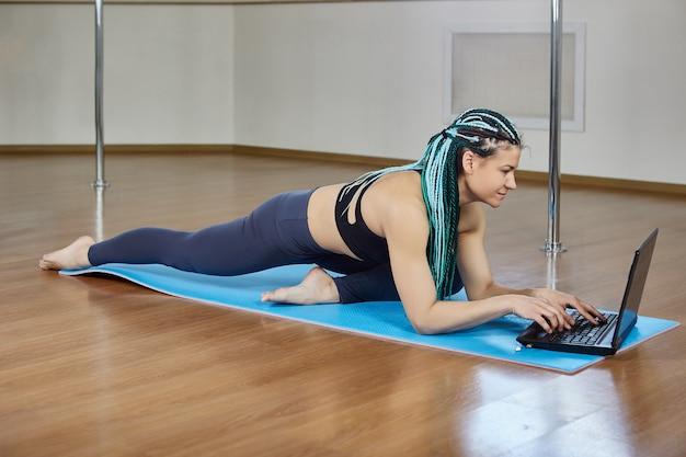 ノートパソコンでオンラインレッスンを使用して女性のトレーニング