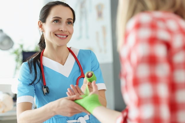 クリニックで若い女性患者の負傷した腕を包帯する女性外傷学者