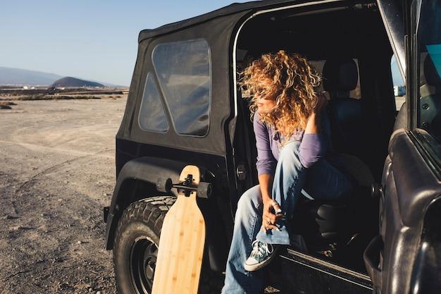 黒い車とロングボードテーブルで一人旅の女性
