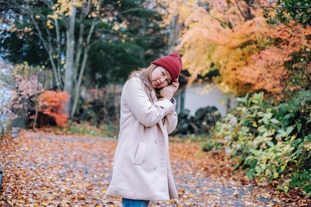 女性旅行し、写真を撮る紅葉、秋のシーズン