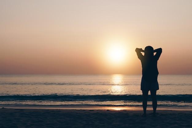 여성은 여름 일몰 해변의 자유를 누리며 전 세계를 여행하고 삶의 개념을 이완합니다.