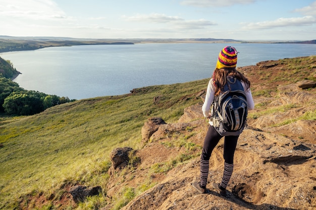 Woman travel blogger in a funny hat from nepal mountain hiker with backpack hike walking on orange huge stones landscape lake and hills