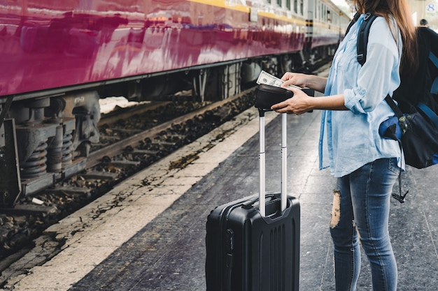 Woman travel by train, girl with backpack us dollars money in hand