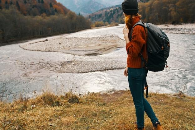 女性は川とバックパックの帽子のセーターの休暇の近くの秋の自然の山を旅行します