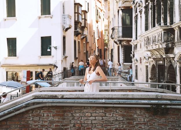 女性旅行イタリア女の子はヴェネツィアの景色を楽しむヴェネツィアの街を歩く女性観光客