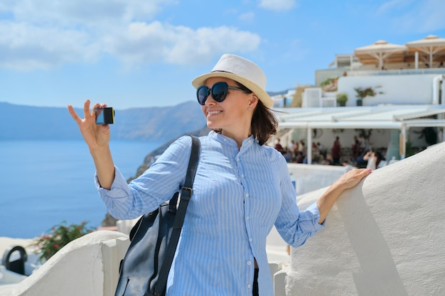 Woman travel vlogger traveling in greek village of oia on santorini island, filming video