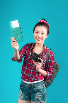 Woman travel. young beautiful asian woman traveler holding passport and air ticket standing over blue.