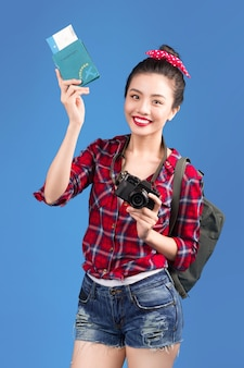 Путешествие женщины. молодой красивый азиатский путешественник женщины держа паспорт и авиабилет стоя над синью.