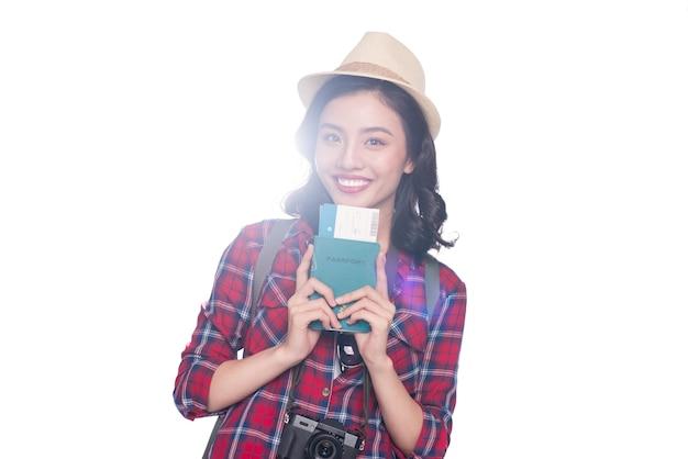 여자 여행입니다. 흰색 위에 서 있는 여권과 항공권을 들고 있는 젊은 아름다운 아시아 여성 여행자.