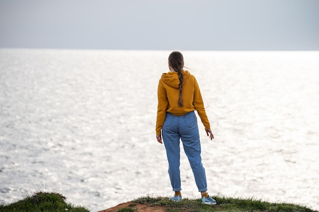 A woman traveler in a bright yellow sweatshirt and loose jeans stands on the seashore and looks into the distance. freedom and a sense of tranquility. love of travel