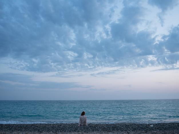 Женщина-путешественница у океана на пляже и море на фоне облаков.