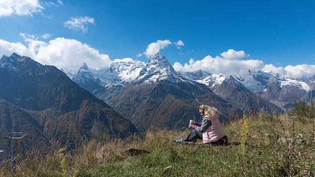 山の風景を眺めながらコーヒーを飲む女性旅行者