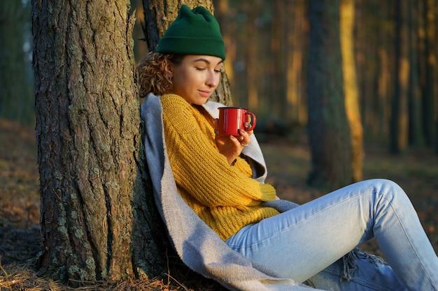 여성 여행자는 가을 숲에서 하이킹을 한 후 뜨거운 차 또는 커피 한잔과 함께 나무에 앉아 일몰을 즐깁니다.