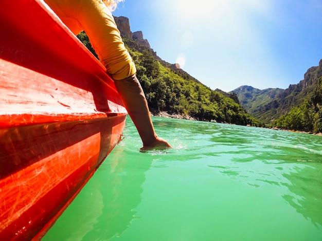 水中と山を背景に手を浸しながら峡谷でカヤックに乗るのを楽しんでいる女性旅行者。明るい晴れた日にカヌーを漕ぎながら湖の水に手を浸す女性