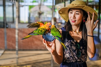Woman traveler feeding many parrot by hand in the bird cage.