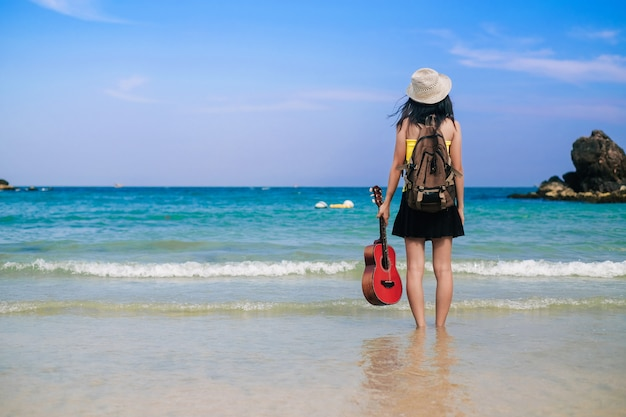 Woman traveler have a bag and guitar standing on the beach