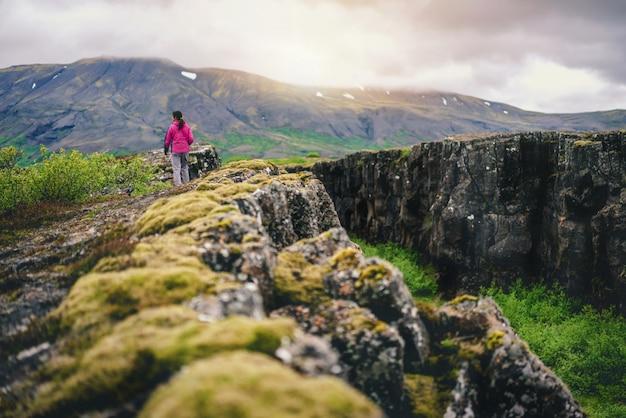 Woman traveler hiking across iceland landscape.