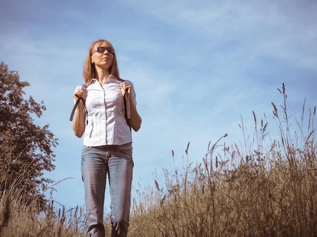 高山草原でバックパックでハイキング女性旅行者。旅行ライフスタイルコンセプトアドベンチャー夏休み屋外。
