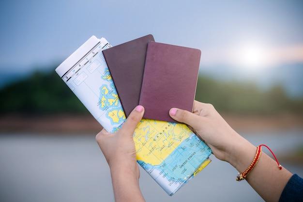 Женщина путешественник держит паспорт с картой