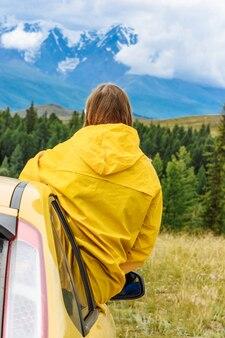 Путешественница в машине на фоне заснеженных гор