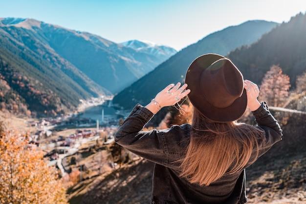 フェルト帽と黒いデニムジャケットを着た女性旅行者がトルコ旅行中に山とトラブゾンのウズンゴル湖の上に立つ