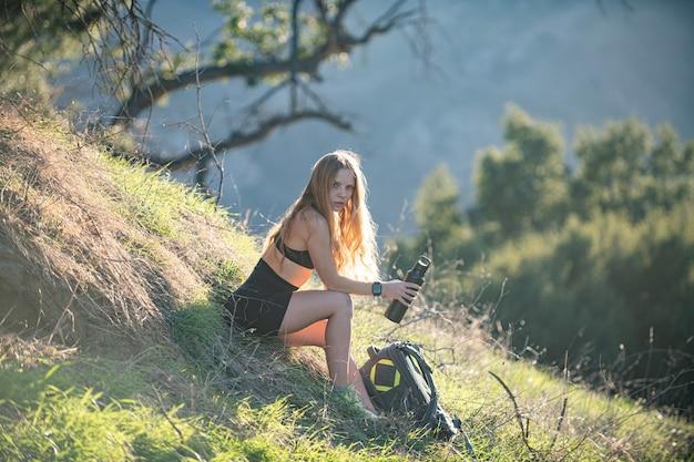 山の女の子のハイキングでバックパックとバトゥール火山インドネシアの女性ハイカーを見ている女性旅行者...