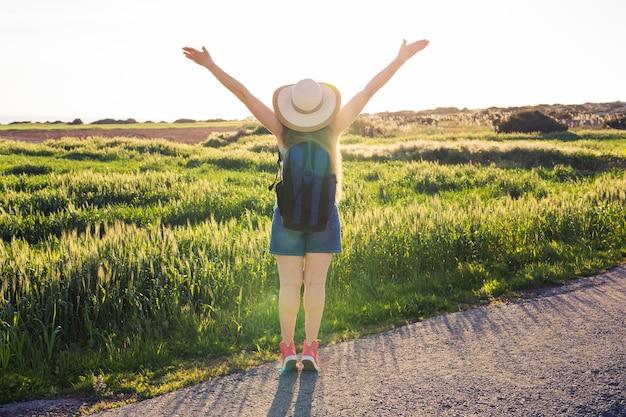 緑の野原の後ろ姿で夕日を見ている女性旅行者