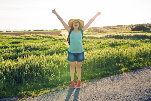 緑の野原で夕日を見ている女性旅行者