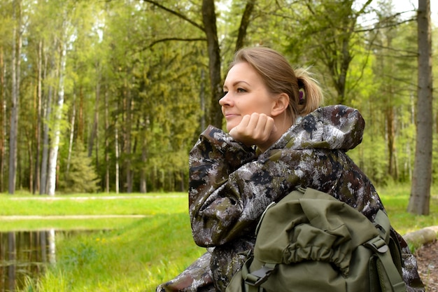 Woman traveler looks at the lake on the nature in summer. camping on a pond in the forest.