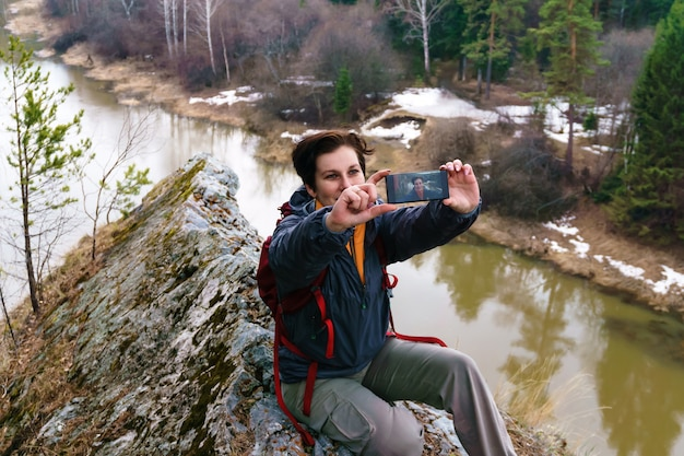 春の川の上の崖の上で女性旅行者が自分撮りをする