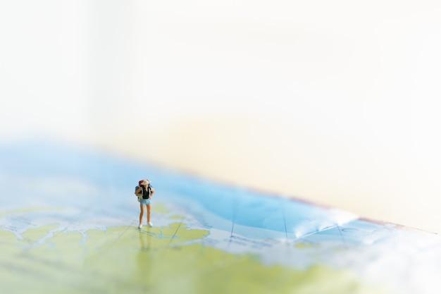 Женщина путешественник миниатюрная фигура люди с рюкзаком, стоящие на карте мира