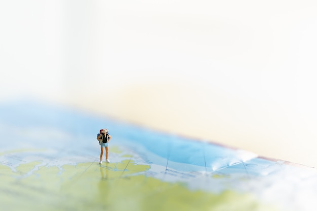 Woman traveler miniature figure people with backpack standing on world map