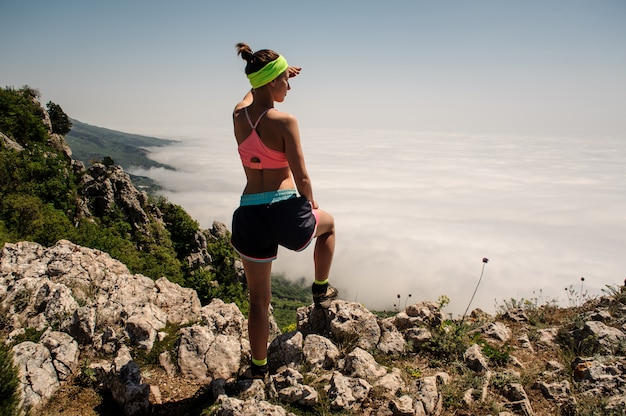 Woman traveler on mountain summit over clouds travel lifestyle