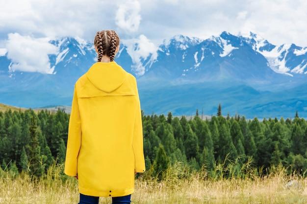 눈 덮인 알프스 산맥의 배경에 여자 여행자. 휴가 및 여행 개념