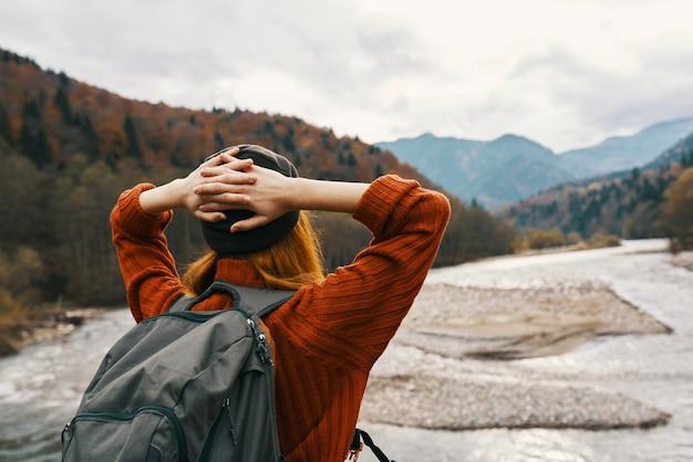 강 근처 자연에서 산에서 휴가에 여자 여행자는 그녀의 머리 뒤에 손을 잡으십시오